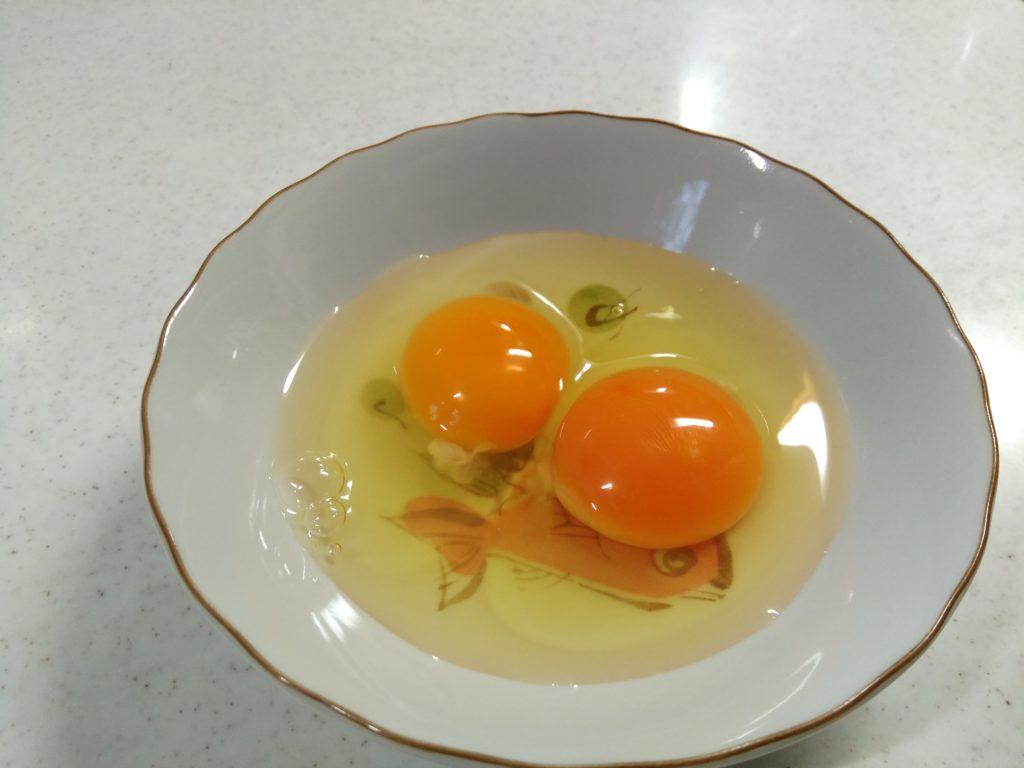 皿に入った生の普通の卵と養生卵
